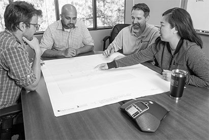 Rahul Deodhar, Wes Ploof, and Shana Holtan working on a building plan