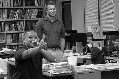 Matt Gillett watching as Miguel Romero shoots a finger dart in the Albuquerque office