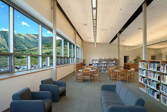 Seating area and bookshelves inside of the library in Aspen Middle School with mountains in the background