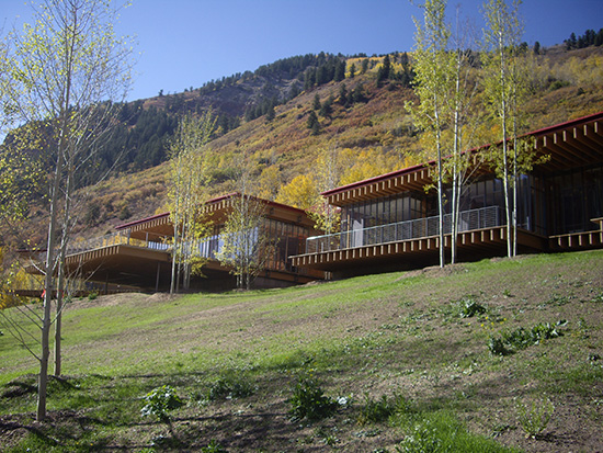 View of a luxury home on a hill in Aspen, CO with mountains in the background