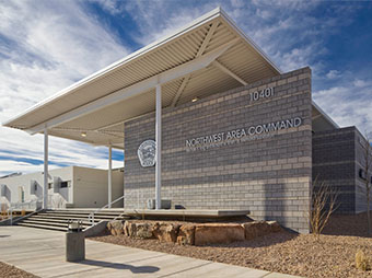 Exterior signage and stairway leading into the Albuquerque Police Station Northwest Command Center with clouds in the background during the day