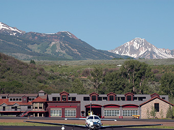 View of a plane parked outside of the Aircraft Rescue and Fire Fight Facility with mountains in the background