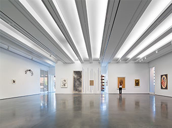 Gallery with a polished concrete floor and art on the walls inside of the Aspen Art Museum