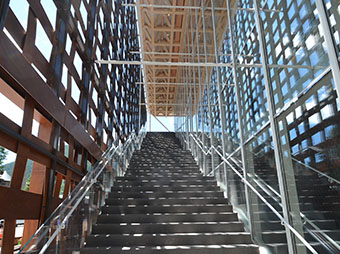 Staircase leading to the entrance of the Aspen Art Museum with lattice walls on the left and glass on the right