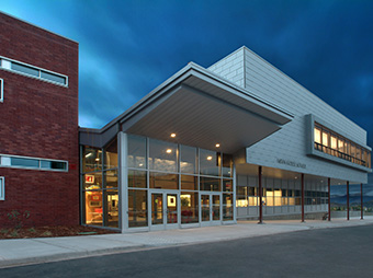 Front entrance to the Aspen Middle School at night with interior lights on