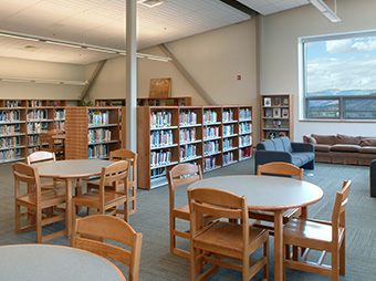 Seating area inside of the library at Aspen Middle School with a mountain view in the background