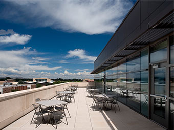 Patio seating on the 4th floor of the Colorado State University Behavioral Science Building in Fort Collins with clouds and campus views