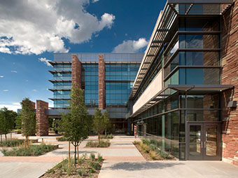 Side entrance into the Colorado State University Behavioral Science Building in Fort Collins with landscaping and clouds
