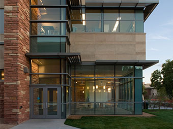 Entrance to the Colorado State University Behavioral Science Building in Fort Collins at dusk with the interior lights on