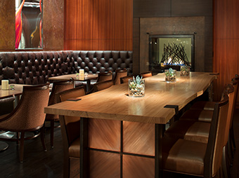 Hightop bar and booth seating with fireplace inside of Elway's Steakhouse at the Ritz Carlton