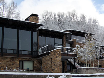 Luxury home in Aspen, CO with snow covered walls and railings