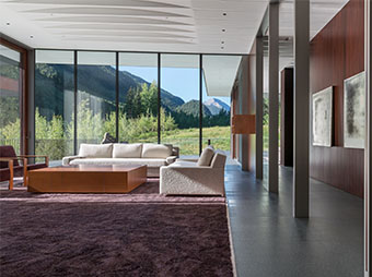 Living room view of the mountains in the background inside of the PT Ranch luxury home in Aspen, CO