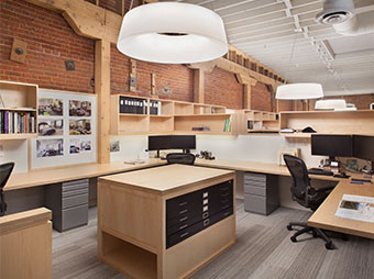 Lighting and four-pack cubicles with central desk inside of the Rowland and Broughton Downtown Denver office building