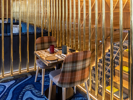 The linear grazer that is housed in the base of the brass pole screen makes the brass screen sparkle. The backlit mirror at the end of the room allures patrons and creates a sense of wonder. but with a good balcony view of everything that is happening below.