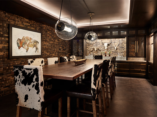 Lighting over dining table with cowhide chairs at Brush Creek Ranch