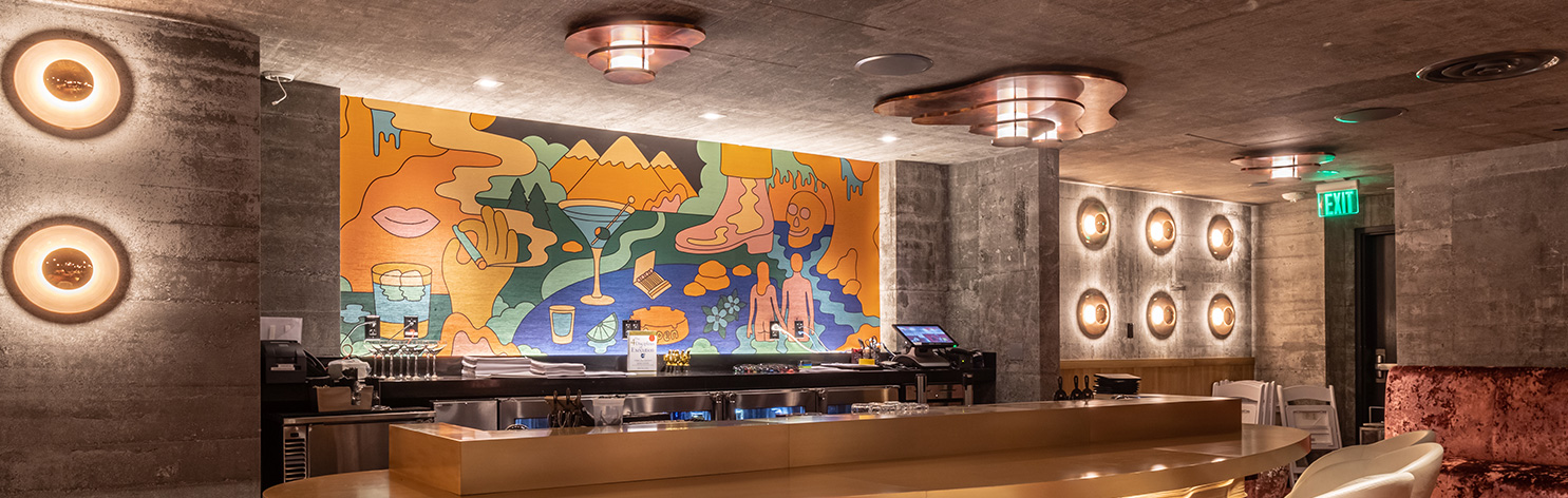 Fun linear grazer is uplighting the mural behind the bar. There are nice circular sconces on the walls with a mirrored element that the light shoots back onto the wall from. There is a nice linear under bar grazer at the front of the bar to highlight the texture once again.