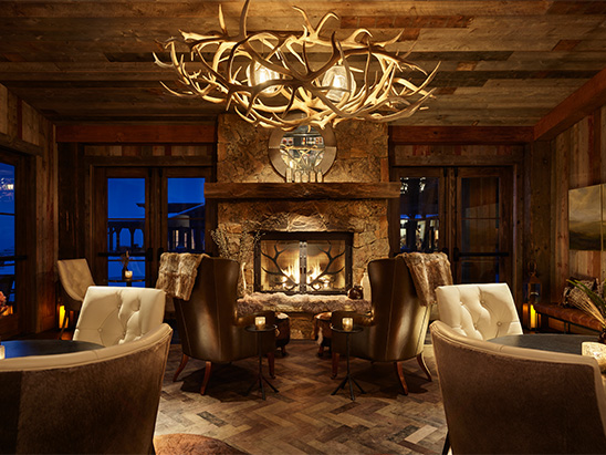 Lounge area with custom antler chandelier in Brush Creek Ranch