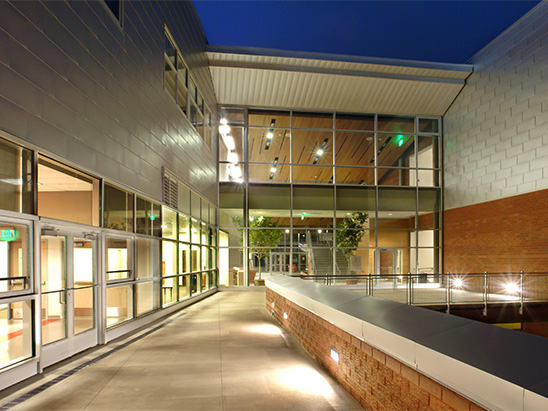 Exterior view of the Aspen Middle School walkway at night where BG provided MEP, lighting, and commissioning services