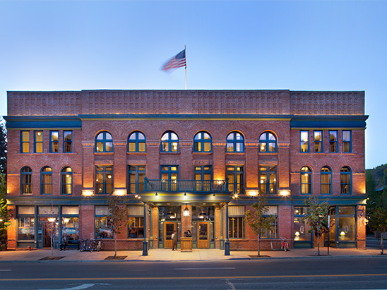 Hotel Jerome lit up at night where BG provided MEP, Lighting, and Technology services